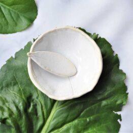 biała ceramiczna miska ze szpatułką na glinki